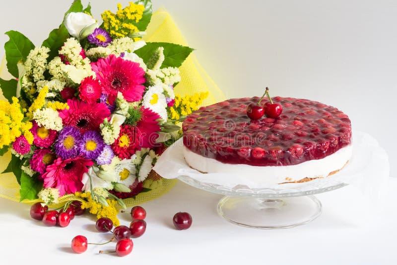 Smakelijke koude kaastaart met kersengelei en bloemen, gelukkige verjaardag stock fotografie