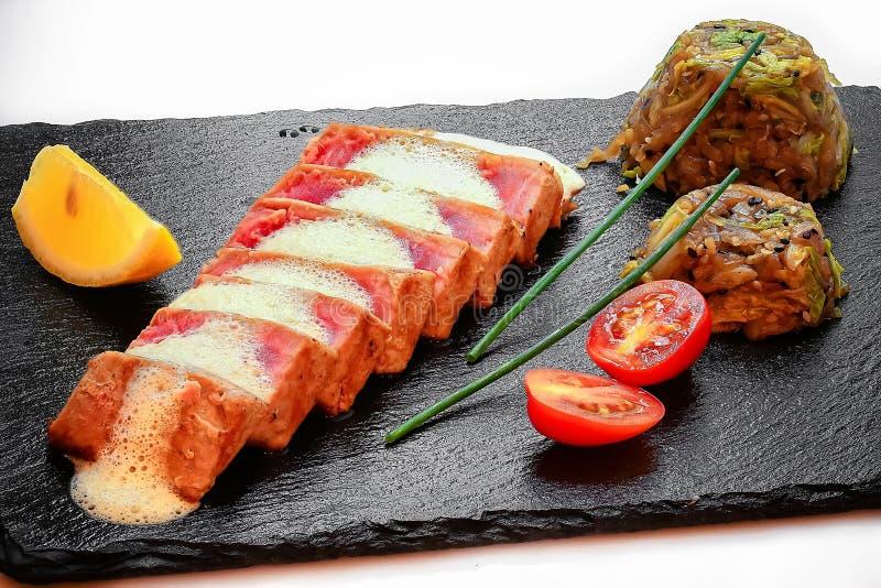 Smakelijke lichtjes geroosterde tonijn met geroosterde groentenclose-up stock fotografie