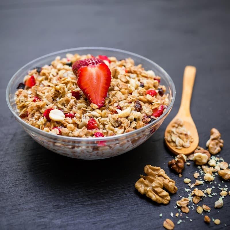 Smakelijke muesli met aardbeien en bosbessen op donkere lijst Vlakte van het dieet legt de natuurlijke ontbijt, hoogste mening stock foto