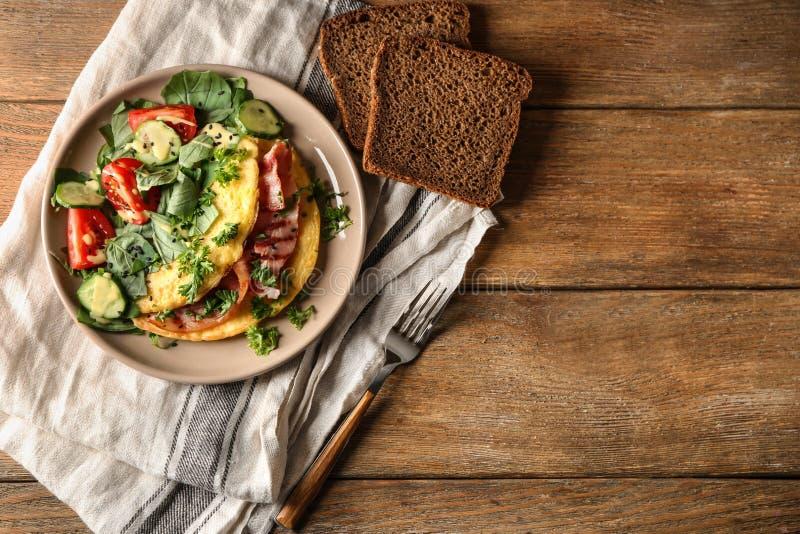 Smakelijke omelet met bacon en groenten op plaat stock foto