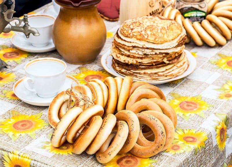 Smakelijke smakelijke ongezuurde broodjes, stapel gebraden pannekoeken, samovar en Ta royalty-vrije stock afbeeldingen