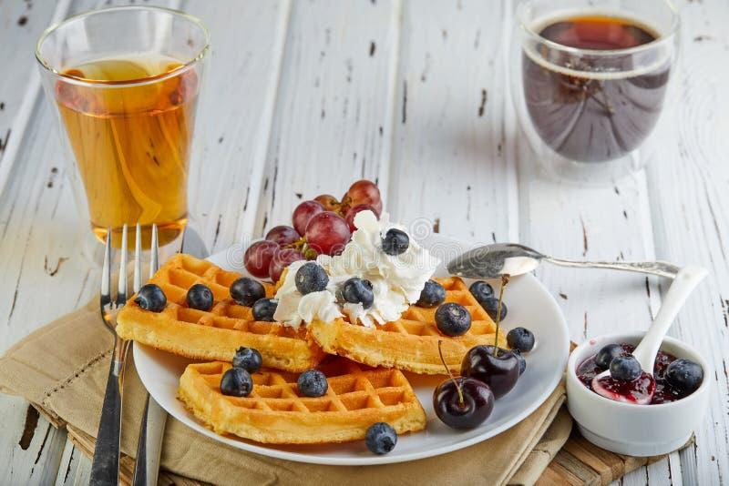 Smakelijke ontbijt Belgische wafels met slagroombosbessen en jam op een houten wit stock afbeelding