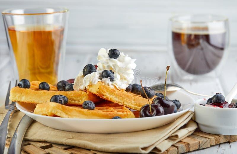 Smakelijke ontbijt Belgische wafels met slagroombosbessen en jam op een houten wit royalty-vrije stock afbeeldingen