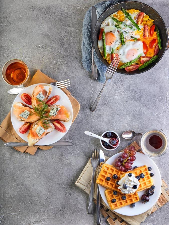 Smakelijke ontbijtroereieren in een pan, sandwiches met stro en kaas en Belgische wafels op een houten wit royalty-vrije stock foto's