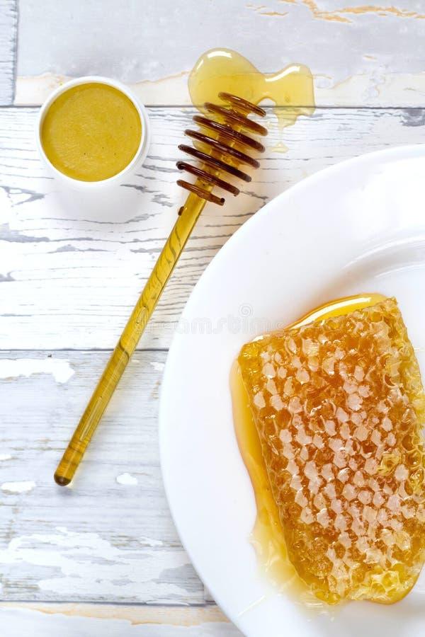 Smakelijke organische honingraat en honingslippenpommade op houten uitstekende achtergrond royalty-vrije stock afbeeldingen