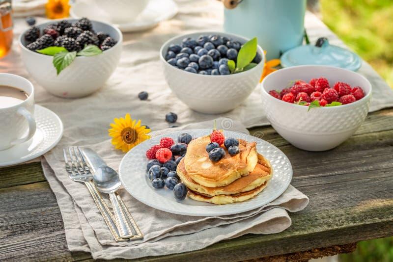 Smakelijke pannekoeken voor ontbijt in de zomertuin stock foto's