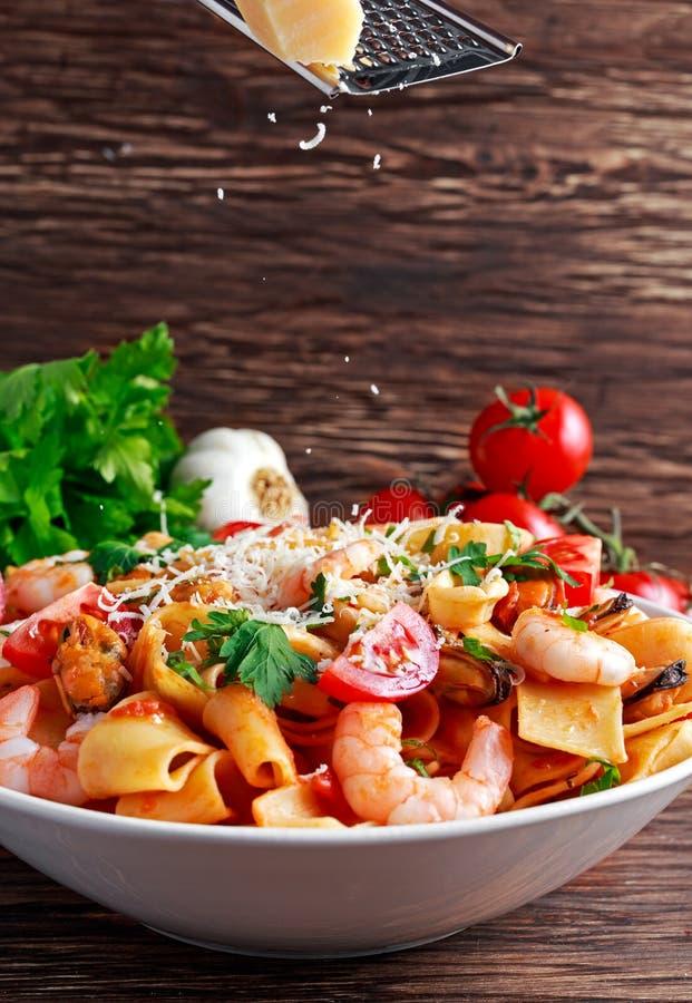 Smakelijke Pappardelle-deegwaren met garnalen, Pijlinktvis, mossel, tomaten en kruiden parmezaanse kaaskaas op bovenkant vaas toe stock afbeeldingen