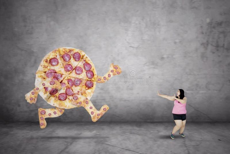 Smakelijke pizza die vette vrouw achtervolgen royalty-vrije stock afbeeldingen