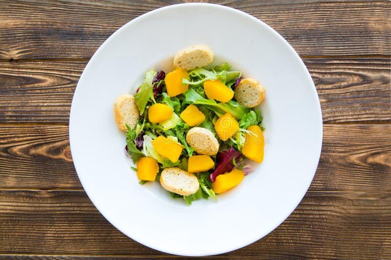 Smakelijke pompoensalade met greens en croutons op bruine lijst stock afbeelding