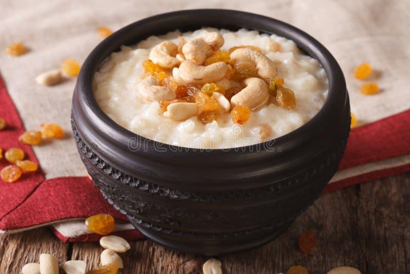 Smakelijke rijstebrij met noten en rozijnen in een komclose-up Hor royalty-vrije stock foto