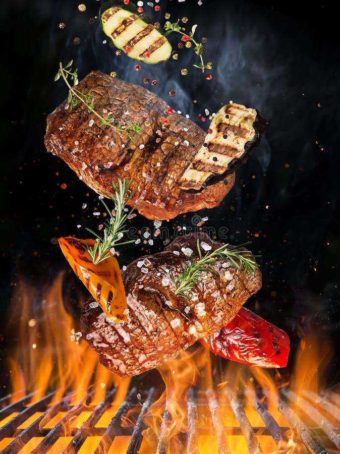 Smakelijke rundvleeslapjes vlees die boven gietijzerrooster vliegen met brandvlammen royalty-vrije stock foto