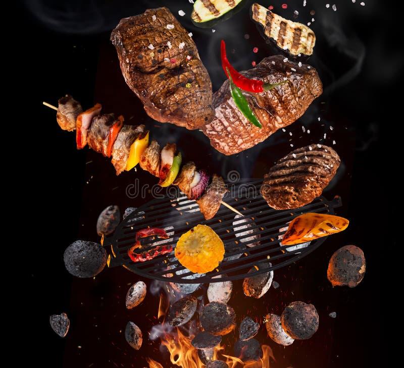 Smakelijke rundvleeslapjes vlees en vleespennen die boven gietijzerrooster vliegen met brandvlammen stock fotografie