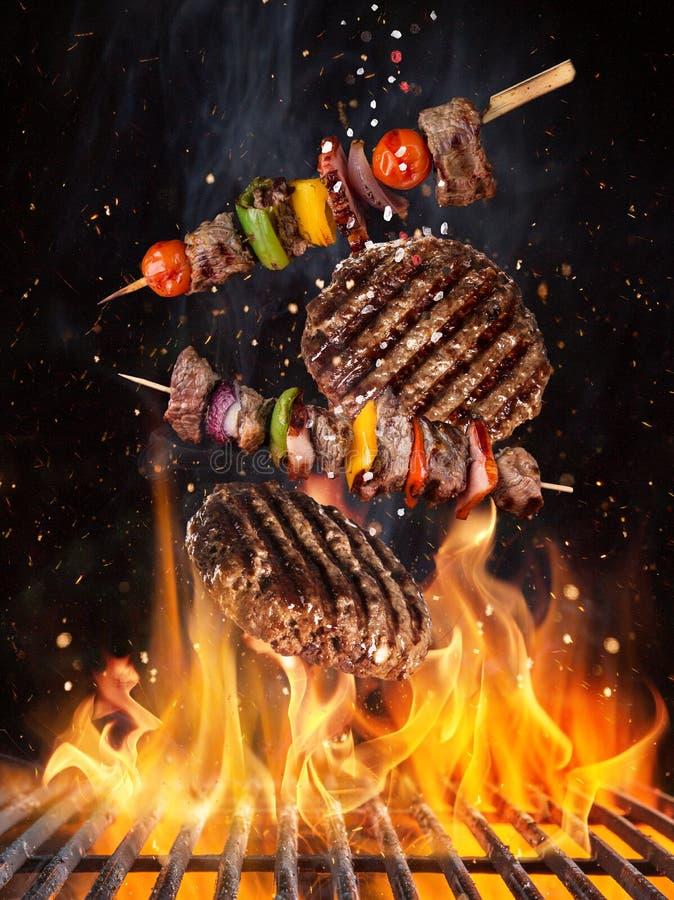 Smakelijke rundvleeslapjes vlees en vleespennen die boven gietijzerrooster vliegen met brandvlammen royalty-vrije stock foto