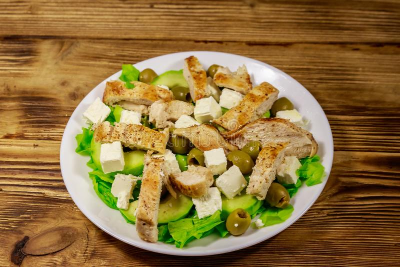 Smakelijke salade met gebraden kippenborst, groene olijven, feta-kaas, avocado, sla en olijfolie op houten lijst stock foto