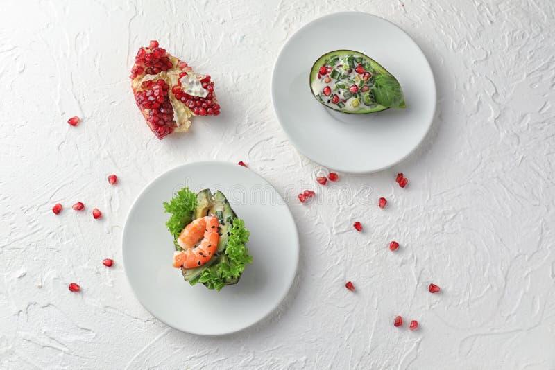 Smakelijke salades in avocadoboten op platen royalty-vrije stock fotografie