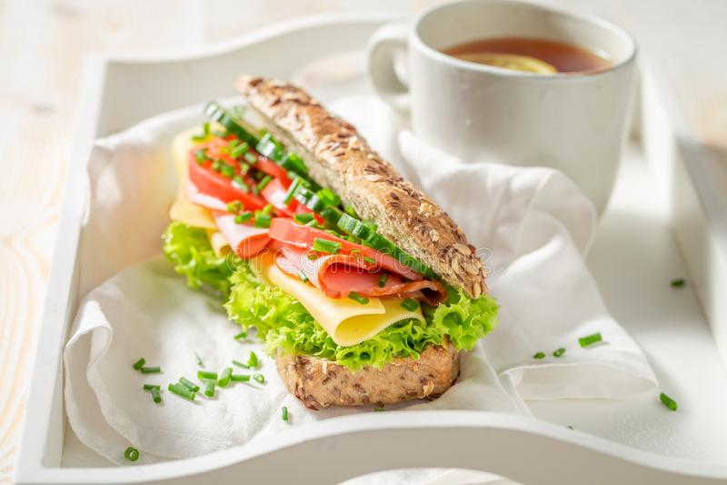 Smakelijke sandwich met ham, bieslook en kaas voor ontbijt stock afbeelding