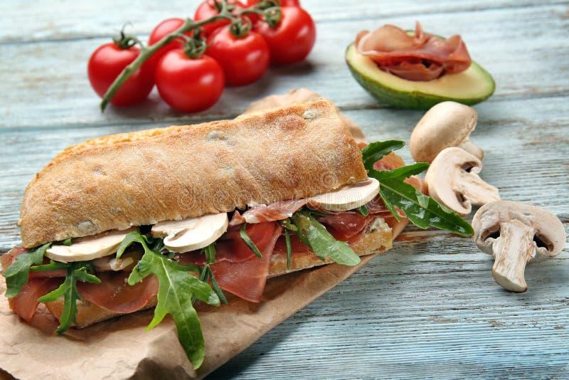 Smakelijke sandwich met prosciutto, arugula en paddestoelen op houten lijst stock afbeelding