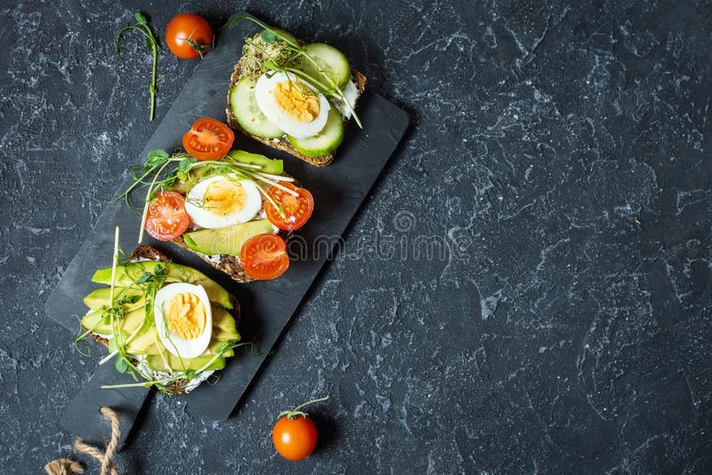 Smakelijke sandwiches met ei, avocado en groenten op steen zwarte achtergrond exemplaar royalty-vrije stock afbeelding