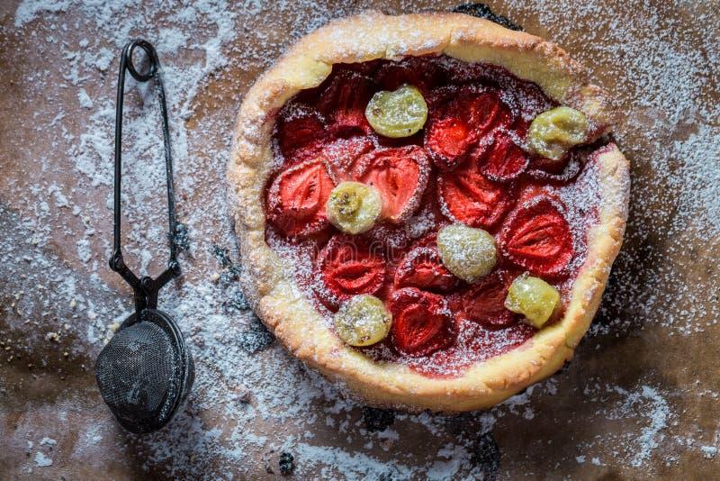 Smakelijke scherp met vruchten en poedersuiker op bakseldocument stock foto