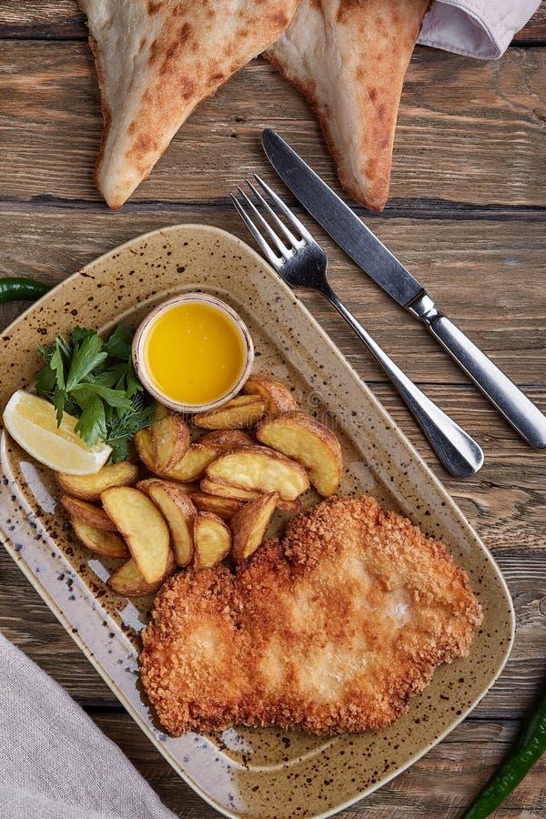 Smakelijke schnitzel met gekookte aardappel De hoogste vlakke mening, legt voedsel royalty-vrije stock afbeelding