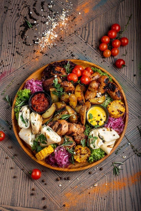 Smakelijke schotel met vlees en groenten, gebakken varkensvlees, cowboygrill, geroosterde aardappels met saus Geassorteerd smakel stock afbeelding