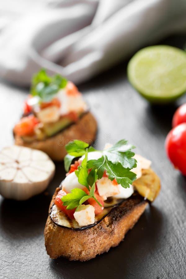 Smakelijke smakelijke tomaten Italiaanse bruschetta, op plakken van geroosterde die baguette met peterselie worden versierd royalty-vrije stock foto's