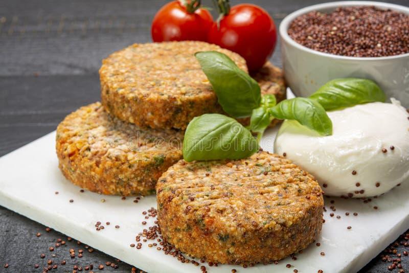 Smakelijke vegetarische burgers maakten van gezonde quinoa, basilicum, tomaten en mozarellakaas stock fotografie