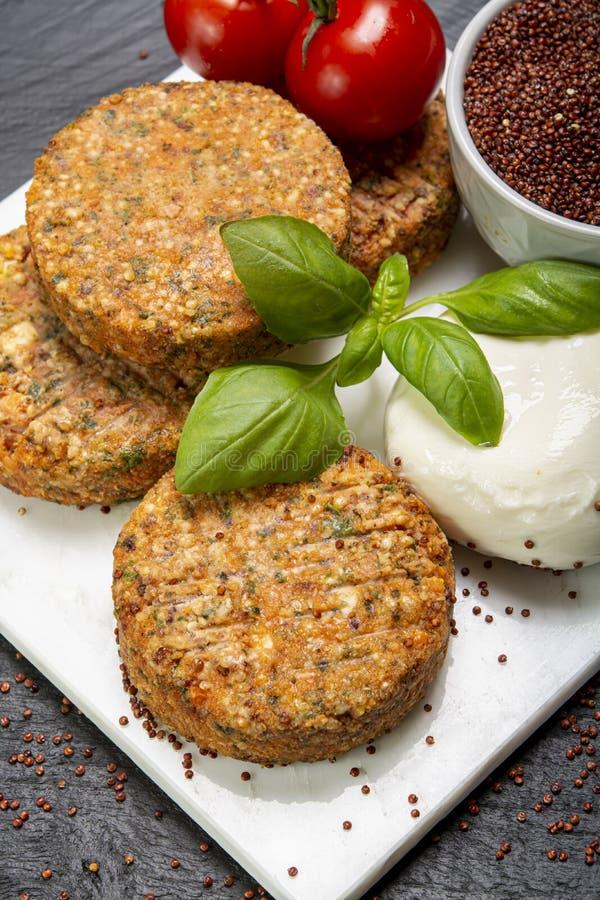 Smakelijke vegetarische burgers maakten van gezonde quinoa, basilicum, tomaten en mozarellakaas royalty-vrije stock fotografie