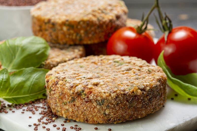 Smakelijke vegetarische burgers maakten van gezonde quinoa, basilicum, tomaten en mozarellakaas stock afbeelding