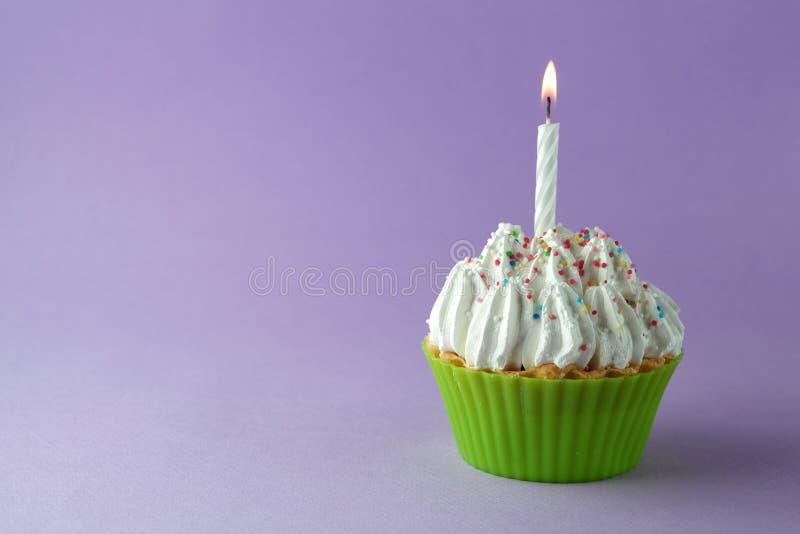 Smakelijke verjaardag cupcake met kaars, op purpere achtergrond, met vrije ruimte stock fotografie