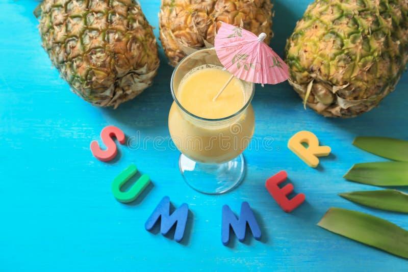 """Smakelijke verse cocktail met ananassen en woord \ de """"Zomer \"""" op blauwe achtergrond stock afbeelding"""