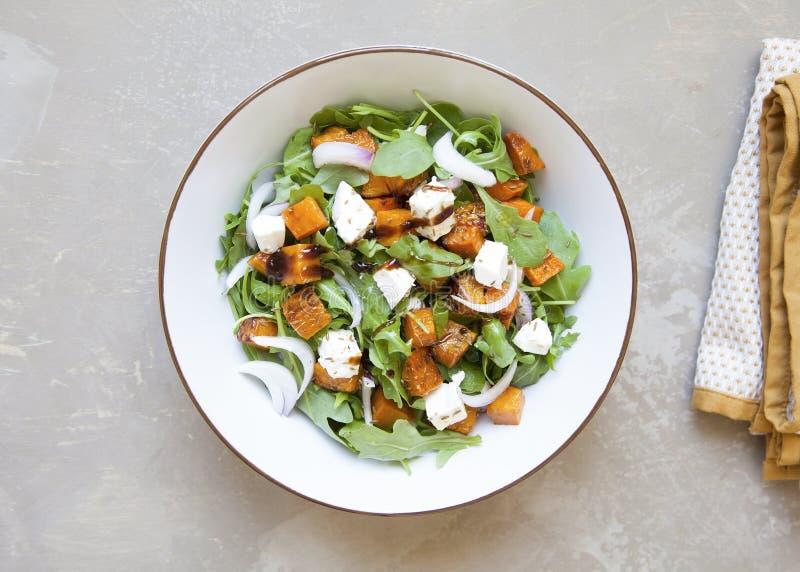 Smakelijke verse salade met gebakken pompoen, feta-kaas, raket en zoete rode ui op bruine achtergrond stock fotografie