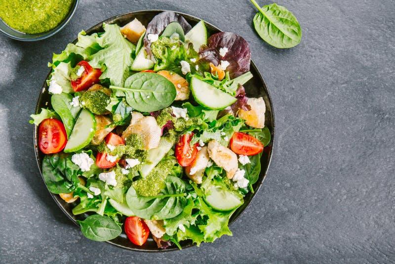 Smakelijke verse salade met kip, pesto en groenten stock foto
