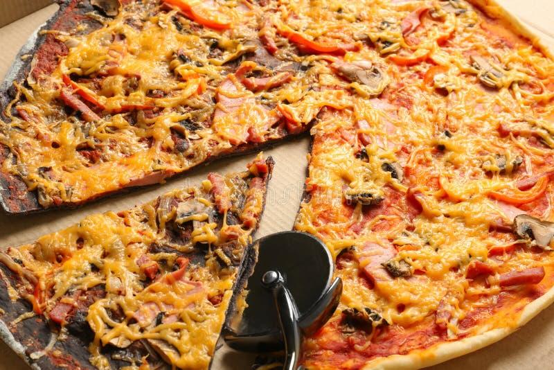 Smakelijke zwart-witte pizza met mes in kartondoos stock foto