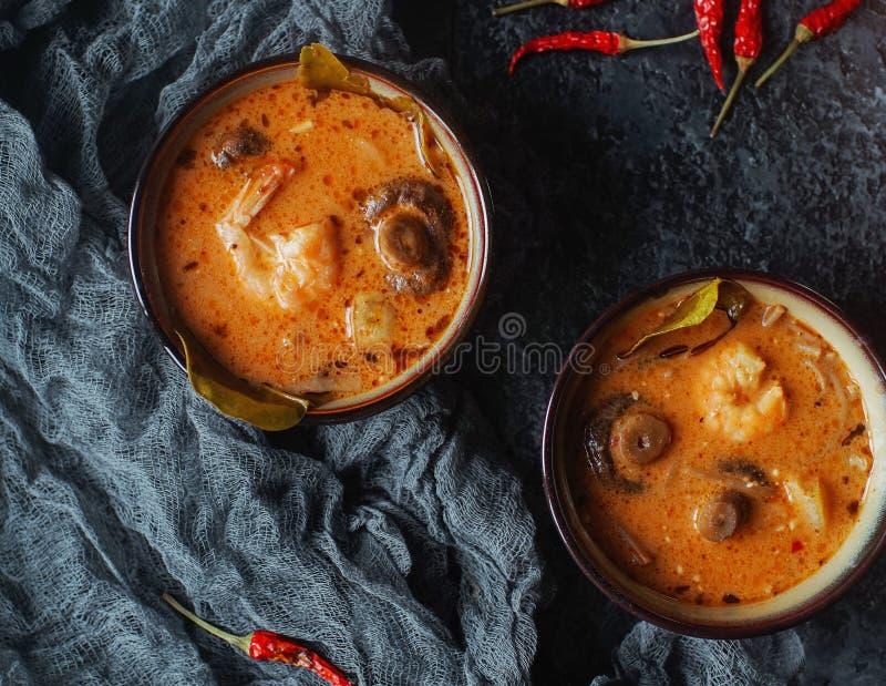 Smaklig asiatisk soppatom sötpotatis i små bunkar med chilipeppar, räka, champinjoner, kokosnöten och limefrukt på en mörk bakgru royaltyfri bild