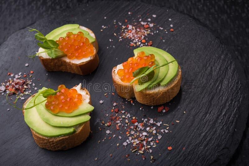 Smaklig bruschetta med avokadot och kaviaren royaltyfri foto