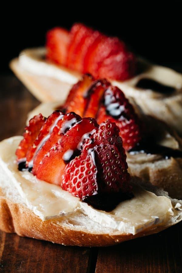 Smaklig bruschetta med nya jordgubbar, bakad brieost och arkivbilder