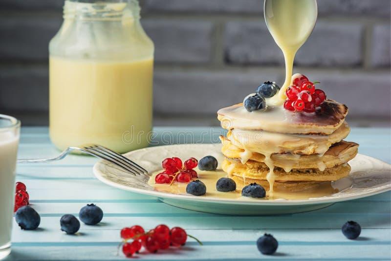 Smaklig frukost med blåbär och vinbär Kondenserat mjölka häller på pannkakor sund l?cker mat N?rbild fotografering för bildbyråer