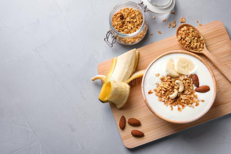 Smaklig frukost med yoghurt, bananen och granola arkivbild