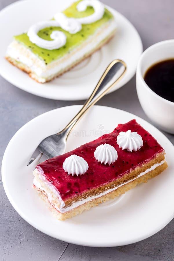 Smaklig frukt och Berry Mini Cakes på den vita plattakoppen kaffe ovanför den smakliga kakan för vertikal smaklig efterrätt royaltyfri fotografi
