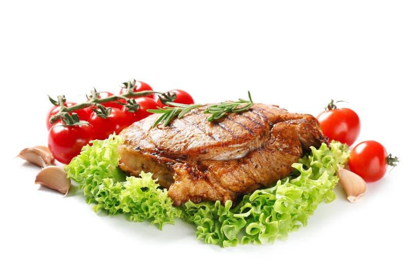 Smaklig grillad biff med nya grönsaker på vit bakgrund arkivbilder
