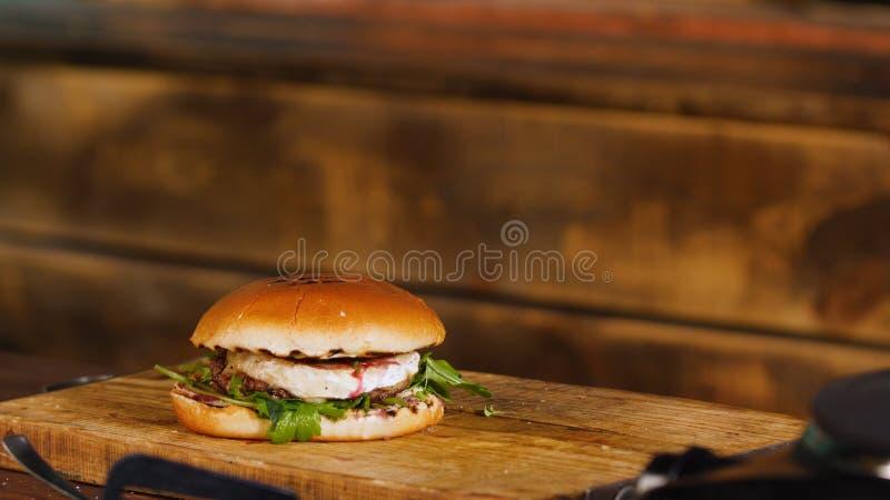 Smaklig hamburgare med nötkött, ost och gräsplaner Materiell?ngd i fot r?knat Klar saftig hamburgare med ost arkivfoto