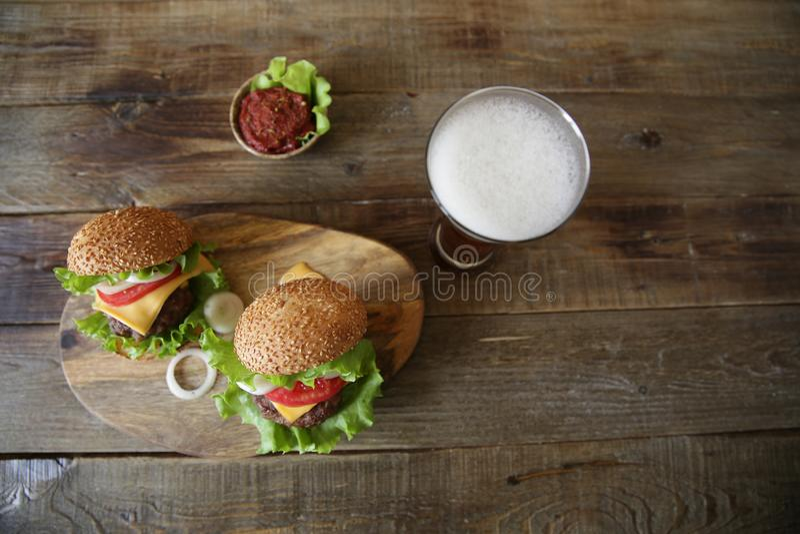 Smaklig hamburgare två med öl på en trälantlig bakgrund med kopieringsutrymme för text Top besk?dar Lekmanna- l?genhet arkivfoton