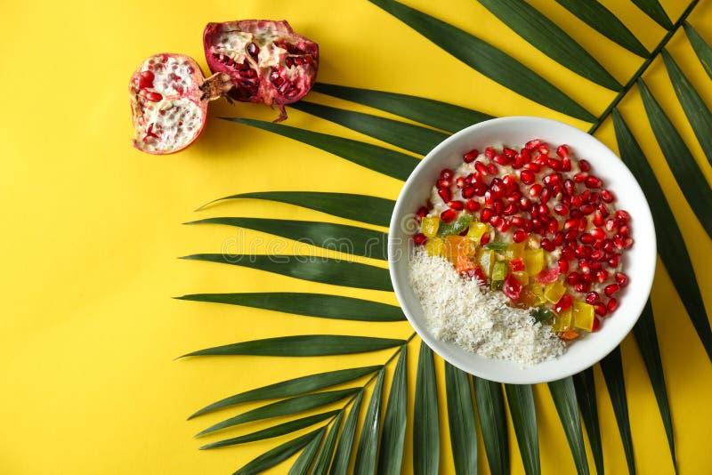 Smaklig havremjöl med granatäpplefrö, succades och det tropiska bladet på färgbakgrund arkivfoton