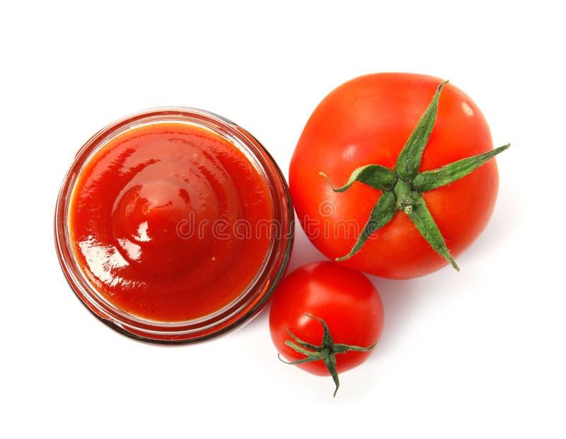 Smaklig hemlagad tomatsås i exponeringsglaskrus och nya grönsaker på vit bakgrund arkivbild