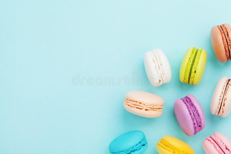 Smaklig kakamacaron eller makron på pastellfärgad bakgrund för turkos från över Färgrika franska kakor på bästa sikt för efterrät arkivbilder