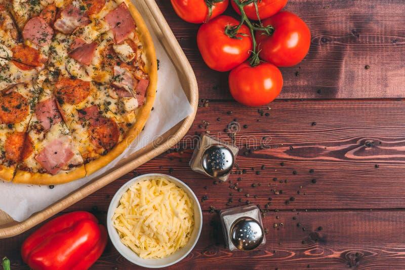 Smaklig ny pizza, bästa sikt, tomater, bulgarian peppar, grated ost, kryddor som ingredienser royaltyfri bild