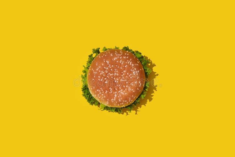 Smaklig ny sjuklig hamburgare med ketchup och grönsaker på gul vibrerande ljus bakgrund Bästa sikt med kopian stock illustrationer