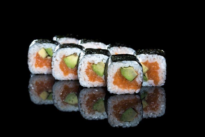 Smaklig ny skullavokadoMaki sushi med ris, avokadot och salmoen royaltyfri foto
