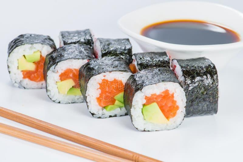 Smaklig ny skullavokadoMaki sushi med ris, avokadot och salmoen arkivbild